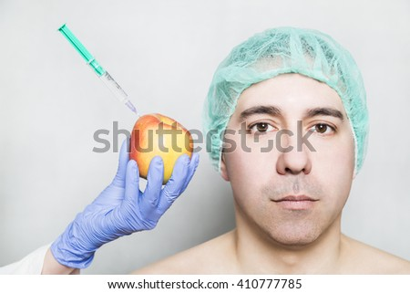 Doctor aesthetician makes hyaluronic acid rejuvenation beauty injections to a red yellow apple near male patient in medical cap. Beautician shows hyaluronic acid is healthy natural and with vitamins. - stock photo
