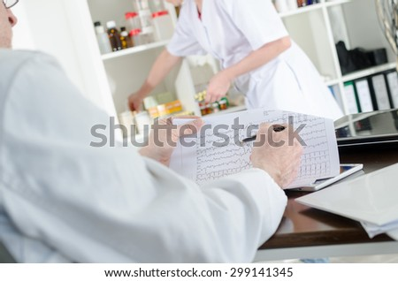 Doctor analyzing an electrocardiogram in medical office