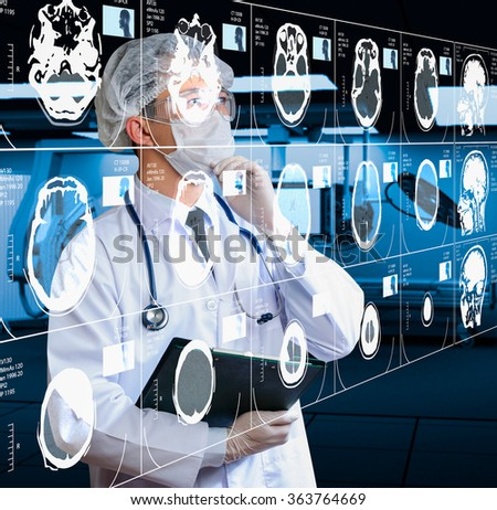 doctor analyzing CT scan result in operating room - stock photo