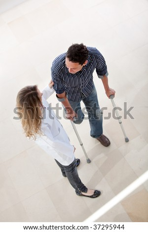 Doctor and a man with crutches in a hospital - stock photo