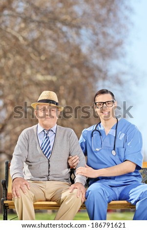 Doctor and a senior gentleman sitting in park - stock photo
