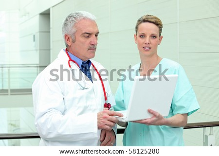 Doctor and assistant in front of a laptop computer