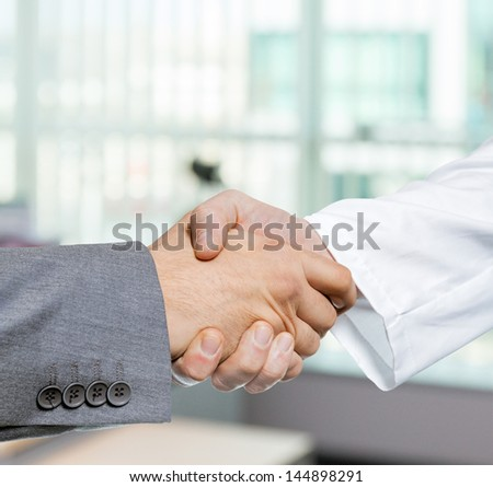 Doctor and businessman shaking hands in office - stock photo