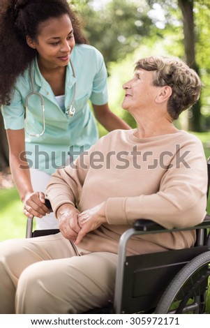 Doctor and disabled woman spending time outdoors - stock photo
