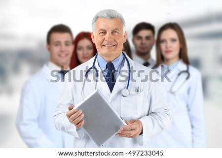 Doctor and medical team on blurred hospital background. Health care concept.