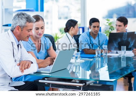 Doctor and nurse looking at laptop with colleagues behind in medical office - stock photo
