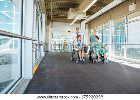 Doctor and nurse pushing patients on wheelchairs at corridor in hospital - stock photo