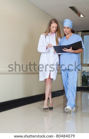 Doctor and nurse reading file while walking in hospital - stock photo