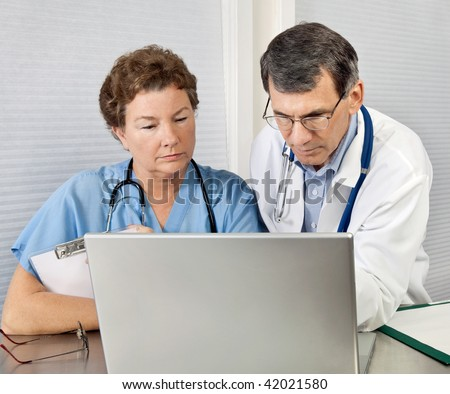 Doctor and nurse reviewing patient information on a laptop computer in an office setting - stock photo