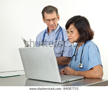 Doctor and nurse reviewing patient information on laptop computer. White background - stock photo