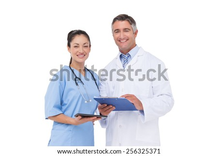 Doctor and nurse smiling at camera on white background - stock photo