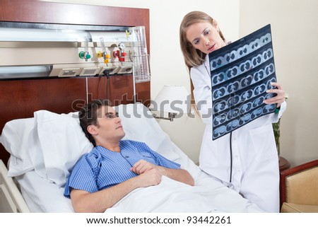 Doctor and patient examining X-ray report in hospital