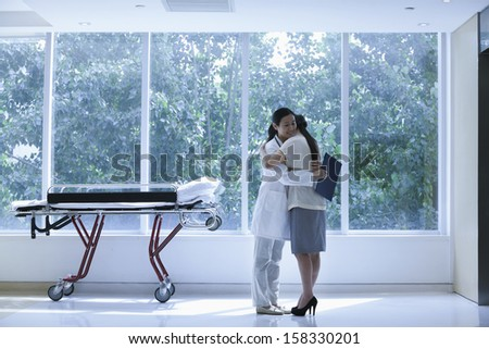 Doctor and patient hugging in a hospital next to a stretcher - stock photo