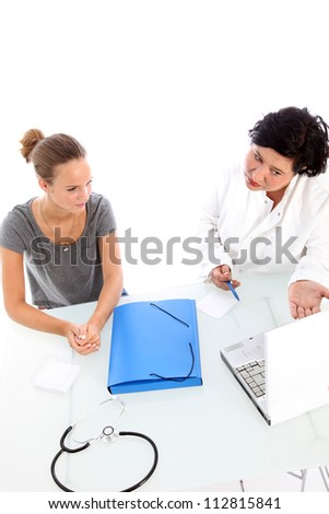Doctor and patient in consultation High angle view of a female doctor and young teenaged patient in consultation with the doctor explaining something in detail with the help of her laptop computer - stock photo