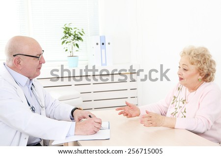 Doctor and patient in hospital clinic - stock photo