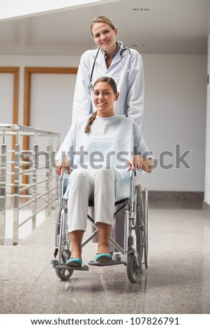 Doctor and patient looking at camera in hospital hallway - stock photo
