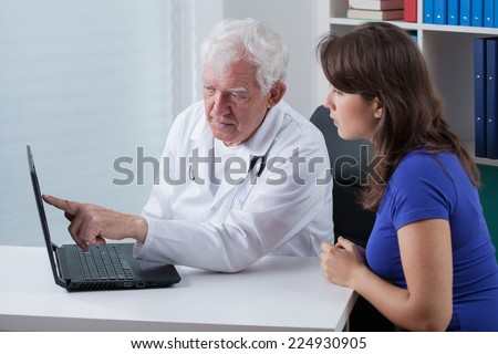 Doctor and patient looking at the laptop - stock photo