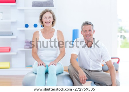 Doctor and patient smiling at camera in medical office - stock photo