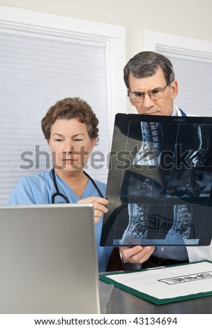 Doctor and Radiologist or Nurse reviewing and discussing patient's MRI scan and comparing with images on the laptop computer. - stock photo