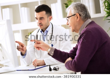 Doctor and senior patient pointing on computer - stock photo