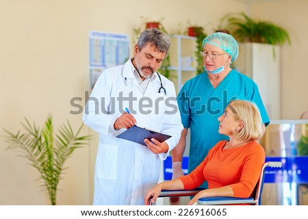 doctor and surgeon consulting patient about medication - stock photo
