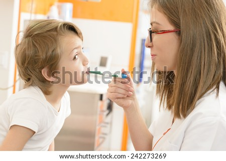 Doctor assistant checking temperature - stock photo