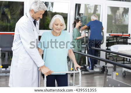 Doctor Assisting Senior Female Patient With Walker In Fitness St