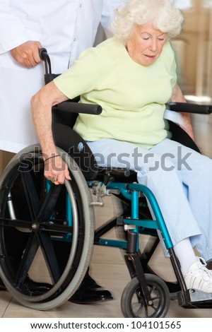 Doctor assisting senior patient sitting in a wheel chair - stock photo