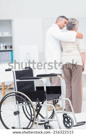 Doctor assisting senior woman to walk with wheelchair in foreground at clinic
