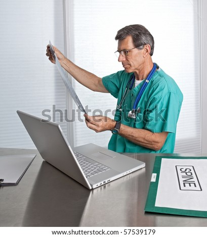 Doctor at computer studying MRI film scans in a clinical setting. - stock photo