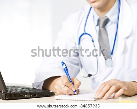 Doctor at his desk close up - stock photo