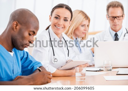 Doctor at the meeting. Beautiful young female doctor smiling while sitting together with her colleagues at the meeting