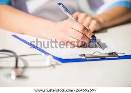Doctor at work, close up of female doctor typing on a computer. - stock photo