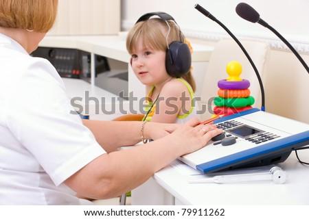 Doctor audiologist testing girl's ears on medical equipment - stock photo