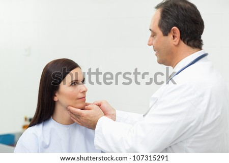 Doctor auscultating the neck of a patient in an examination room - stock photo