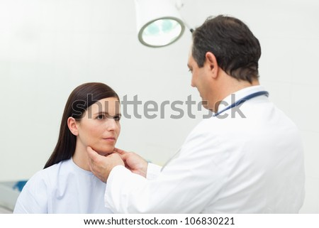 Doctor auscultating the neck of his patient in an examination room - stock photo