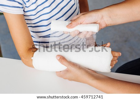 doctor bandaging hand of little patient. medicine, health care and people concept