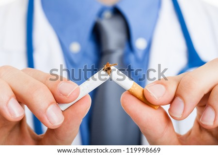 Doctor breaking a cigarette - stock photo