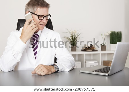 Doctor chatting on his mobile phone while seated at his desk in his office reading information on the screen, of his laptop computer. - stock photo