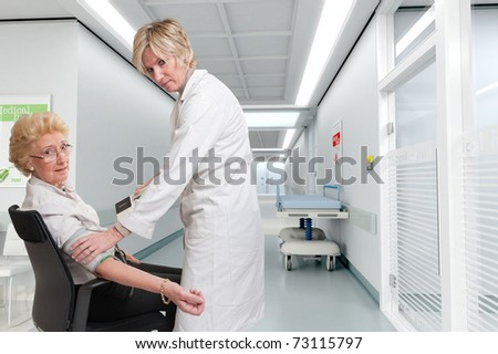 Doctor checking a lady?s blood pressure in a hospital interior