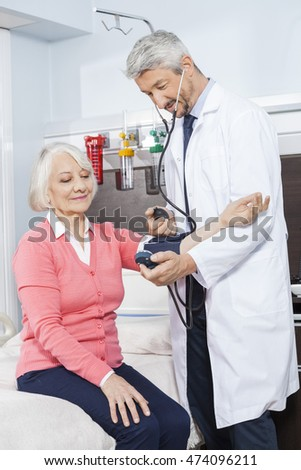 Doctor Checking Blood Pressure Of Senior Patient In Rehab Center