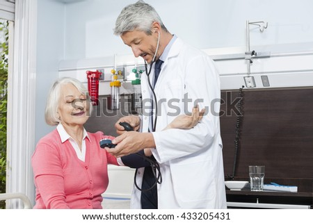 Doctor Checking Blood Pressure Of Senior Woman In Rehab Center - stock photo