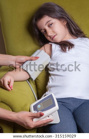 Doctor checking blood pressure of small beautiful middle eastern girl sitting on green chair and feeling bad.