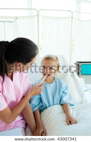 Doctor checking chlid's throat in a hospital