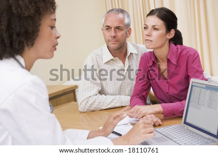 doctor checking couples details - stock photo