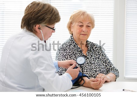 Doctor checking elderly womans blood pressure - stock photo