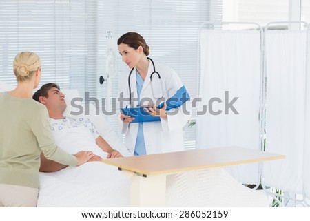 Doctor checking her patient in hospital room - stock photo