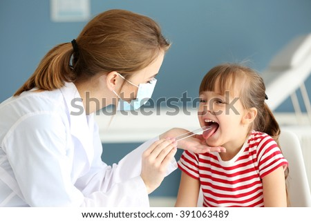 Doctor checking little girl's throat in the office - stock photo
