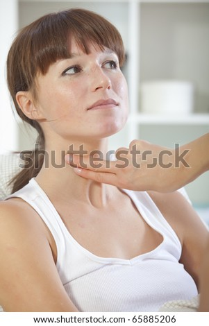 doctor checking pulse with two fingers on female patient - stock photo