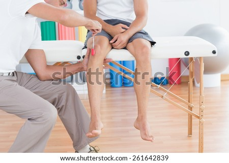 Doctor checking reflexes of the knee of his patient - stock photo